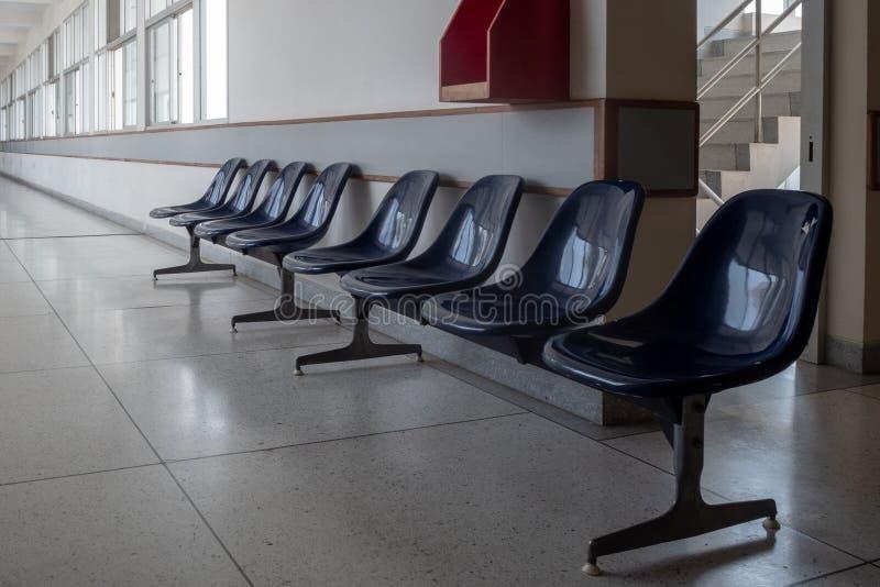 Asientos para el sistema que espera contra la pared en el pasillo vacío imágenes de archivo libres de regalías