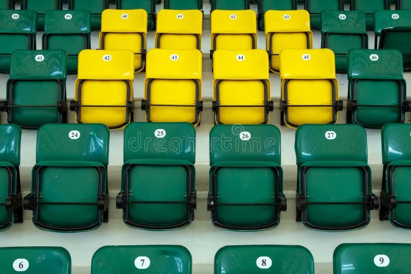 Asientos pl?sticos amarillos y verdes en los soportes del complejo de los deportes Auditorio para las fans de deportes Asientos p imagenes de archivo