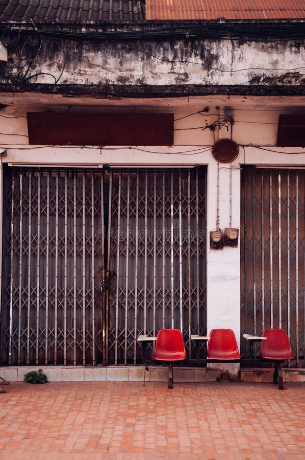 Asientos rojos de la fila de la conferencia y viejo frente constructivo con la puerta del metal fotos de archivo