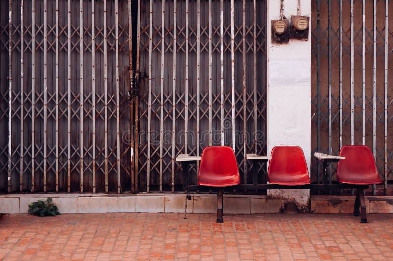 Asientos rojos de la fila de la conferencia y viejo frente constructivo con la puerta del metal foto de archivo libre de regalías