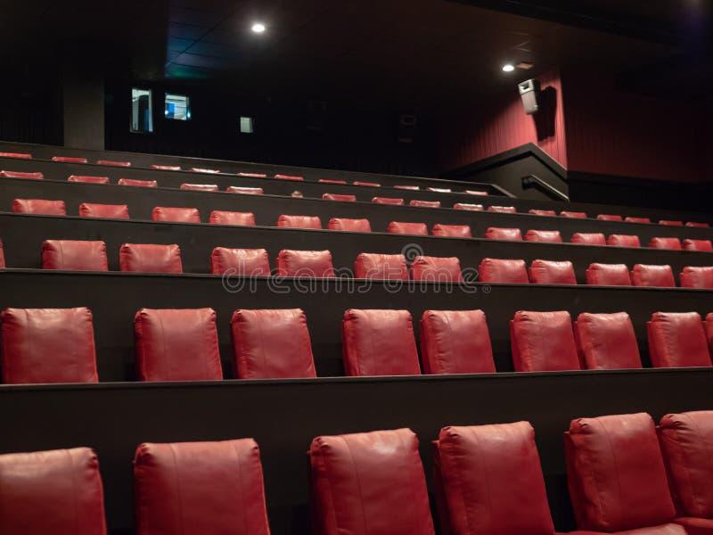 Asientos rojos de lujo del cine con el proyector encendido en fondo fotografía de archivo