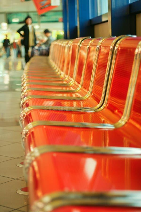 Asientos rojos vacíos del metal en el pasillo del aeropuerto imágenes de archivo libres de regalías