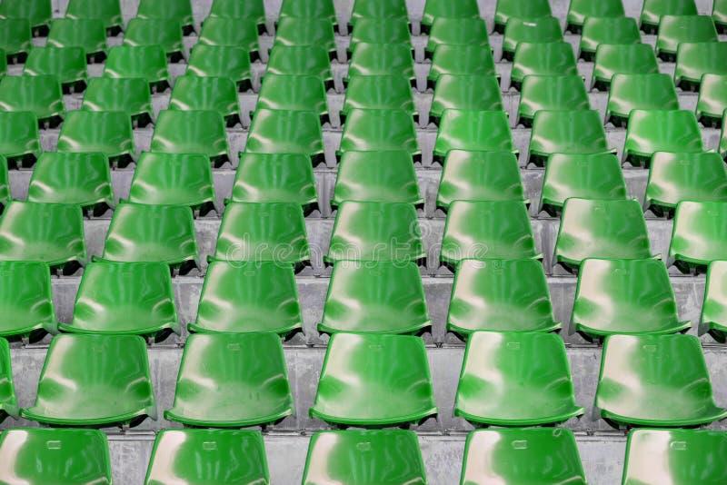 Asientos vacíos verdes del estadio en arena foto de archivo