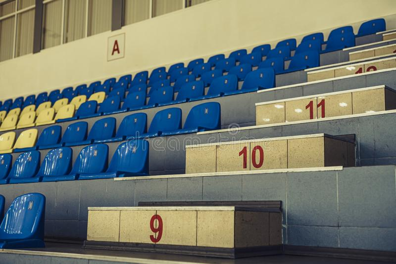 Asientos verdes del estadio Azul de la arena de deporte y asientos plásticos amarillos indoor imágenes de archivo libres de regalías