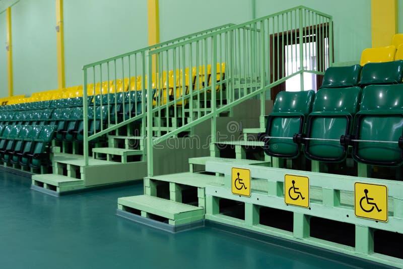 Asientos verdes y amarillos y asientos para los minusválidos Pasillo de deportes de los asientos que asienta Espacio libre Territ imágenes de archivo libres de regalías