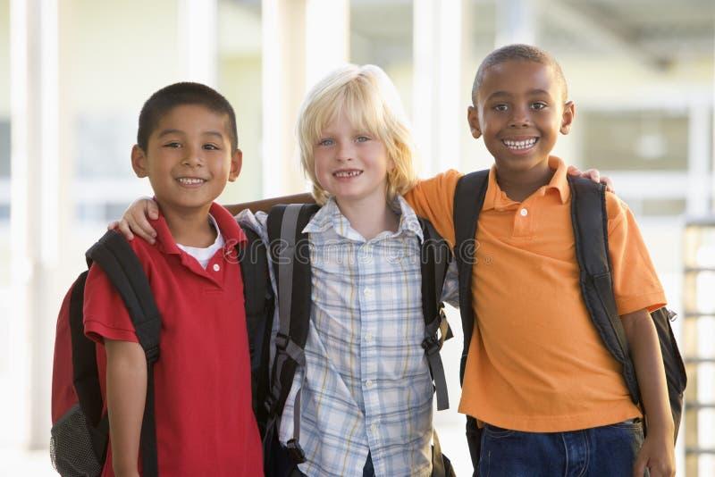 asilo dei ragazzi che si leva in piedi insieme tre immagine stock libera da diritti