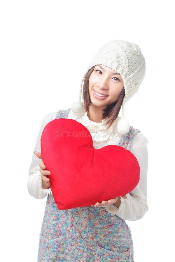 Asimiento de la chica joven una almohadilla del corazón del amor fotos de archivo libres de regalías