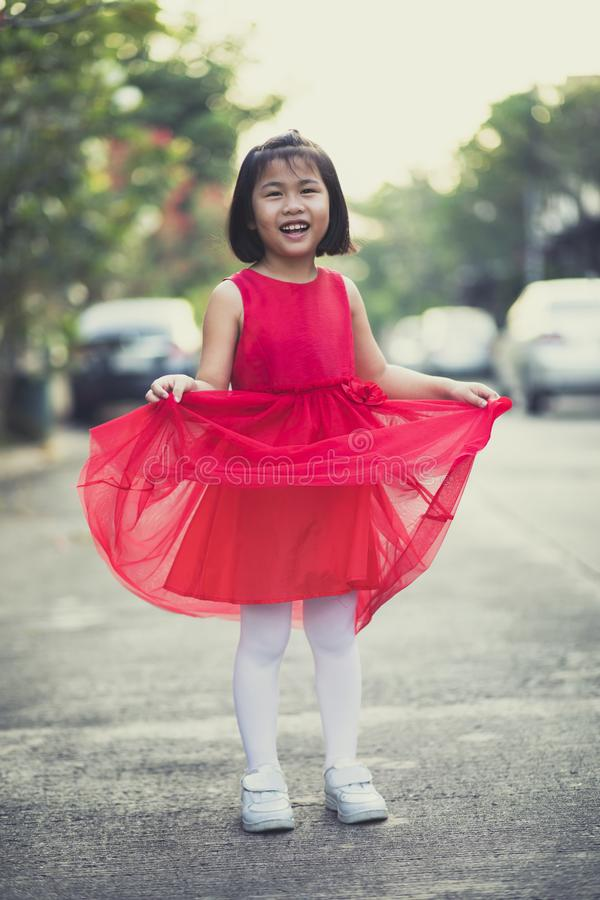 Asina children girl wearing red skirt dress toothy smiling face happiness emotion royalty free stock photography