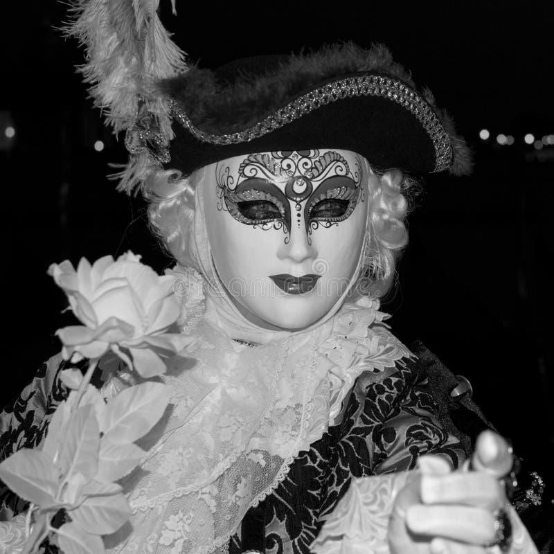 Asistente masculino del carnaval en traje tradicional y máscara que se coloca con de nuevo a Grand Canal, góndolas en el fondo foto de archivo libre de regalías