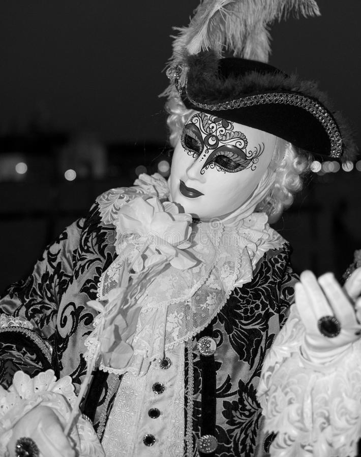 Asistente masculino del carnaval en traje tradicional y máscara que se coloca con de nuevo a Grand Canal, góndolas en el fondo imagen de archivo libre de regalías