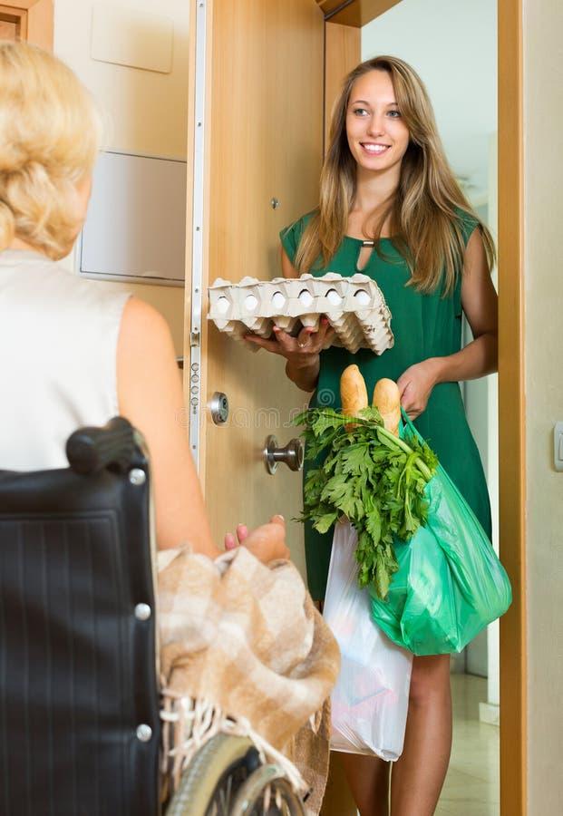 Asistente social que trae la comida a inválido foto de archivo libre de regalías