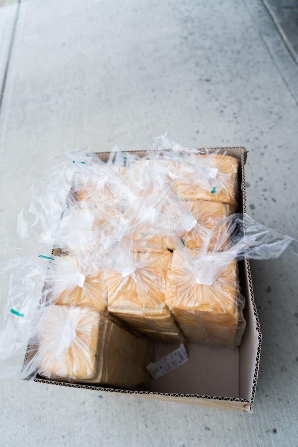Ask av nya loaves av bröd för helt vete som är klart för leverans arkivbilder