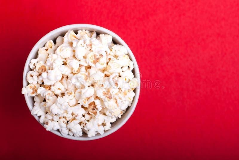 Ask av popcorn på en röd bakgrund, bästa sikt arkivfoto
