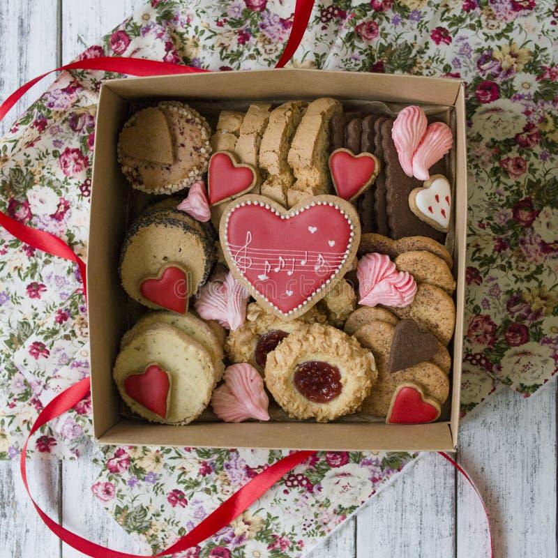 Ask av sötsaker: kakor marshmallow, maräng i en ask på tabellen, kakor i formen av en hjärta en romantisk gåva för royaltyfri foto