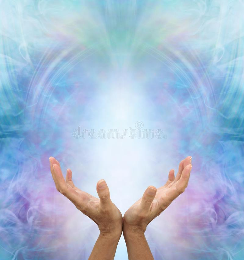 Ask Believe Receive in the Power of Love. Female with hands reaching towards a white light against a beautiful angelic ethereal blue energy background with copy royalty free stock images