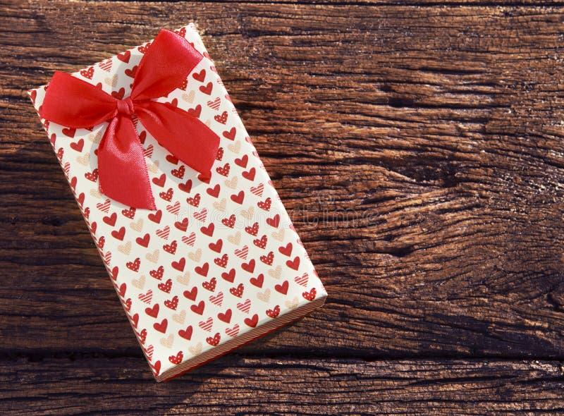 Ask för gåva för hjärtafläckgåva med det röda bandet på gammal wood textur royaltyfri foto