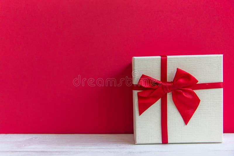 Ask för gåva för Valentine's dag vit med en röd pilbåge på röd väggbakgrund, arkivbild