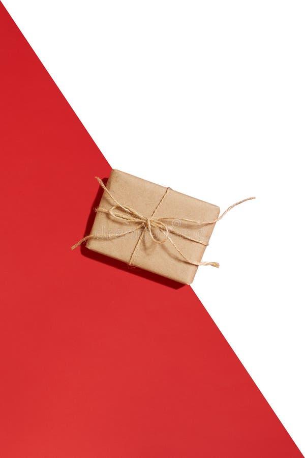 Ask för hantverkpappersgåva som binds från rep på röd och vit bakgrund modell arkivbild