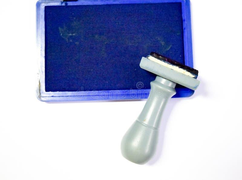 Ask för Rubber stämpel som och för blått färgpulver isoleras på vit royaltyfria foton