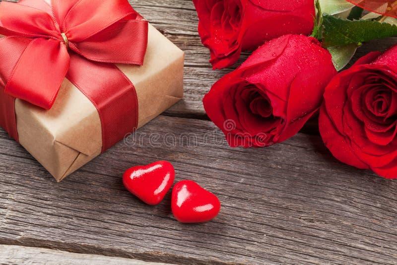 Ask för valentindaggåva, rosor och godishjärtor royaltyfria bilder