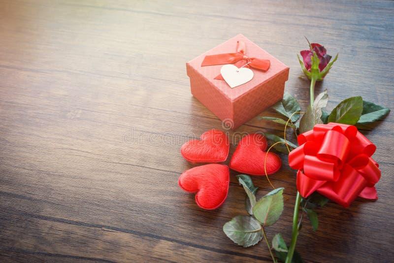 Ask för valentindaggåva som är röd på blomman för dag för valentin för träbakgrund/för romantiker den röda hjärtaröda rosa fotografering för bildbyråer