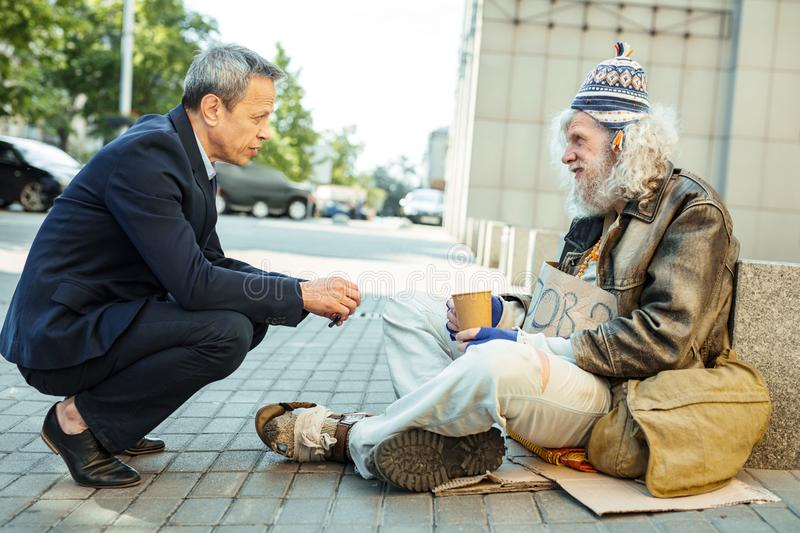 Helpful office worker asking street person about needed food royalty free stock photos