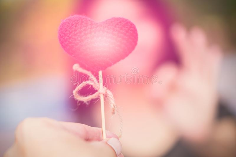 man to give a pink heart to women hand ok at blur background royalty free stock images