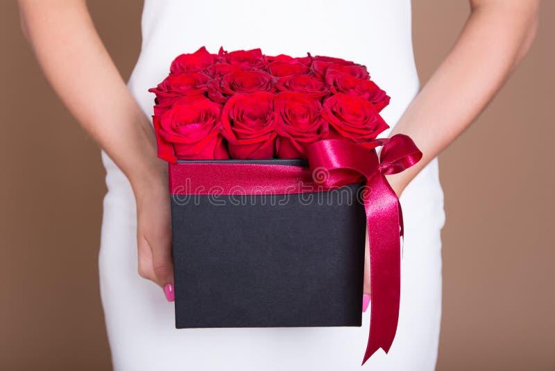 Ask med röda rosor i kvinnliga händer fotografering för bildbyråer