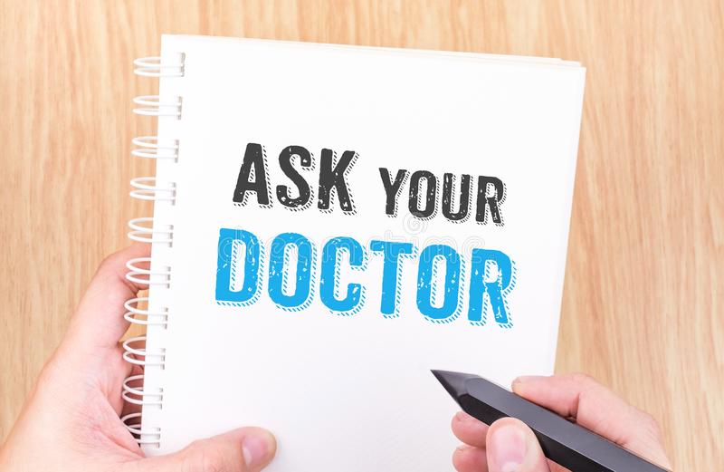 Ask your doctor word on white ring binder notebook with hand holding pencil on wood table,Health card concept royalty free stock photos