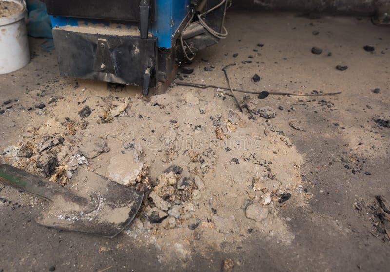 Aska som ligger nära centralvärmeugnen i källare royaltyfri bild