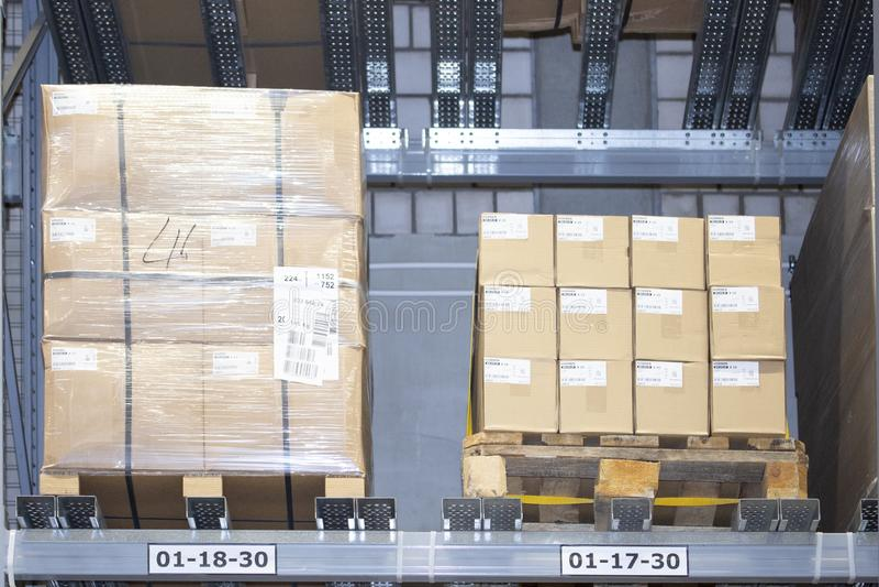 Askar av gods på paletter på hyllorna av ett lagerlager Gods i materielet, lagerlagringsorganisation royaltyfri bild