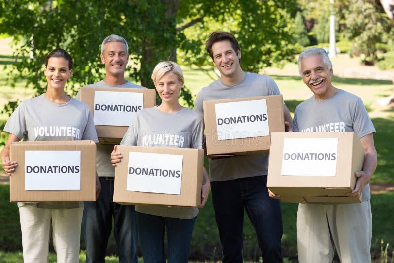 Askar för donationer för lycklig volontärfamilj hållande royaltyfria foton