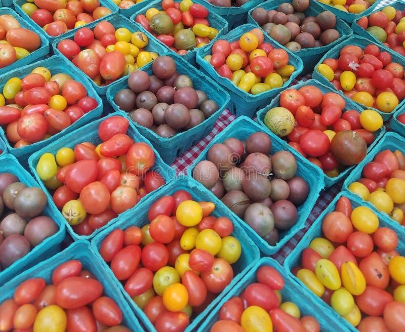 Askar och askar av körsbärsröda tomater arkivfoton