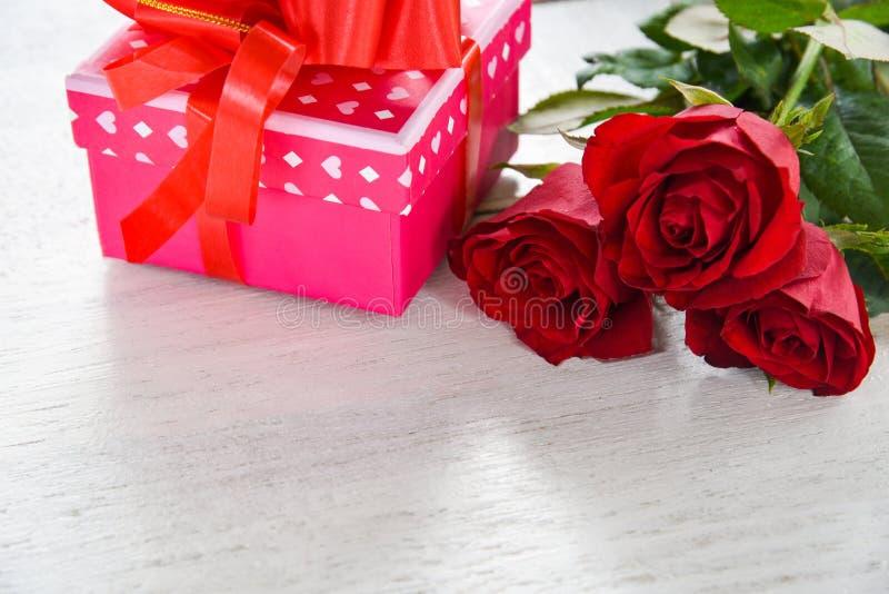 Asken för gåvan för begreppet för förälskelse för blomman för asken för valentindaggåvan blommar den rosa med röda rosor för band royaltyfria bilder