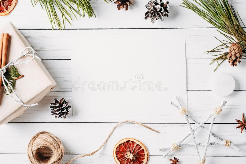 Asken för gåvan för Cristmas garneringwirh, sörjer kottar, torkade apelsiner på en vit bakgrund Bästa sikt, lekmanna- lägenhet, m royaltyfria foton