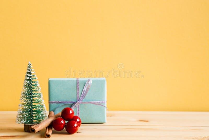 Asken för julprydnadgåvan, sörjer trädet, röda bär på trätabellen royaltyfria bilder