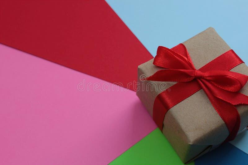 Asken med en röd pilbåge står på papper av olika färger royaltyfria bilder