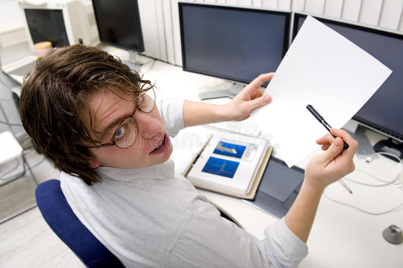 Asking for clarification. A designer asking for clarification of a document, sitting behind his desk and several computers stock photography