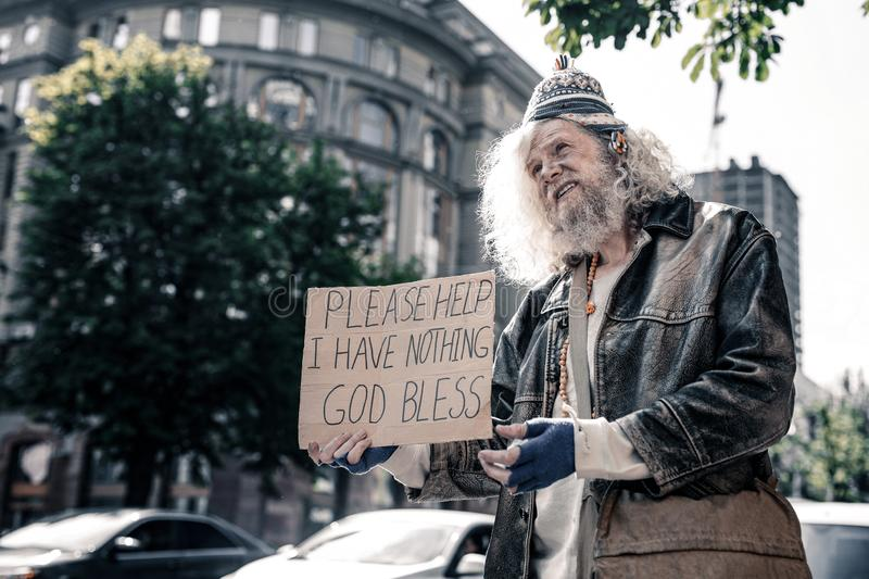 Unhappy long-haired dirty man being jobless and barely staying alive. Asking for support. Unhappy long-haired dirty man being jobless and barely staying alive royalty free stock images