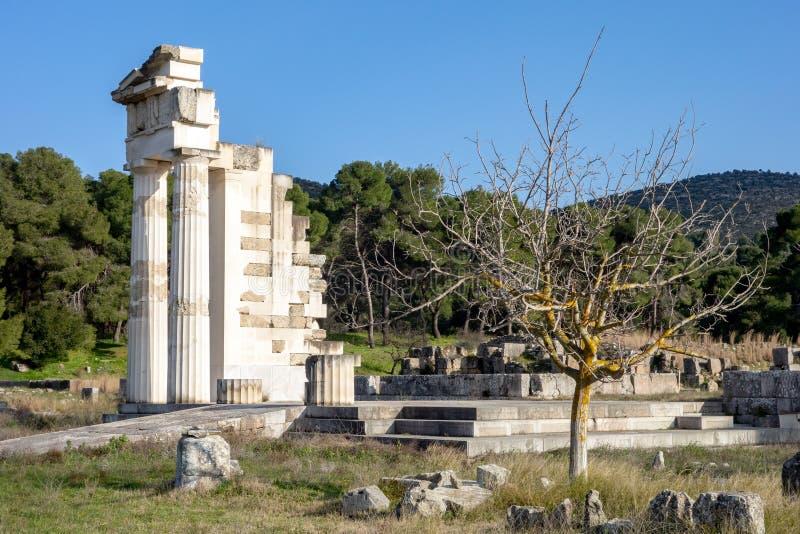 Asklepios-Tempel in Epidaurus mit einem Baum im Vordergrund bei Sonnenuntergang stockbilder