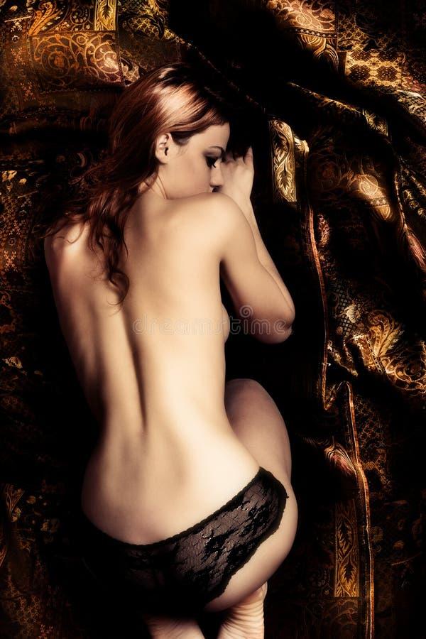 Asleep. Sensual young woman asleep, golden brown background, studio shot stock images