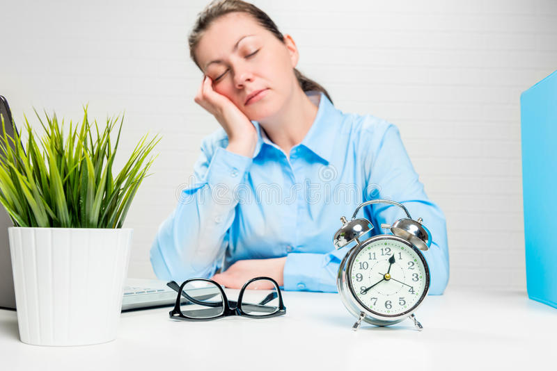 Asleep businesswoman in an office out of focus, alarm clock stock photo