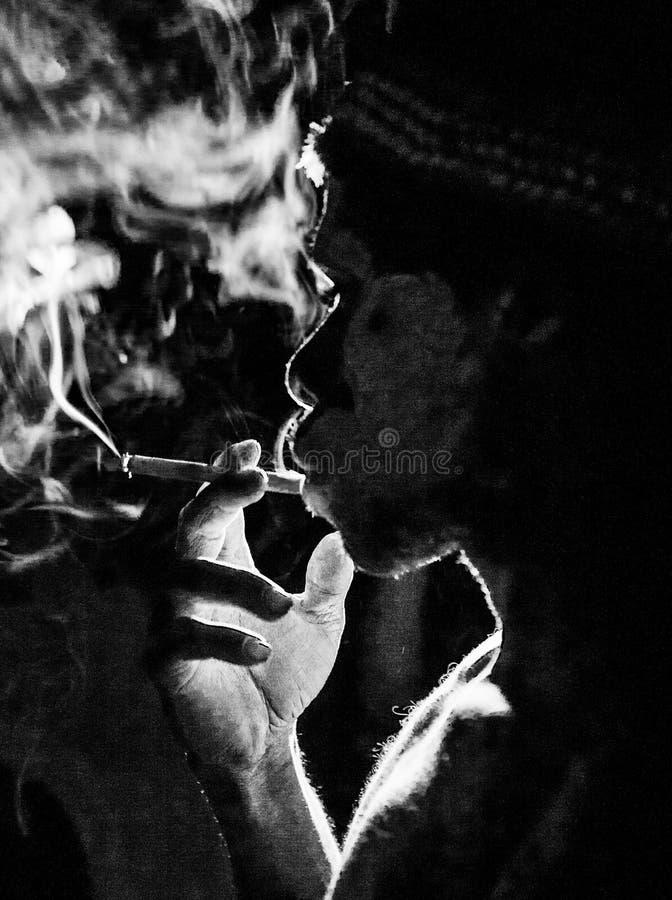 Asmat tribe man smokes in the dark. INDONESIA, IRIAN JAYA, ASMAT PROVINCE, JOW VILLAGE - JUNE 12: Asmat tribe man smokes in the dark royalty free stock images