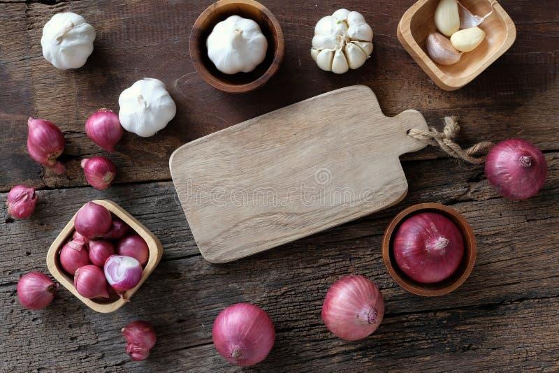 Asortowana świeża organicznie czerwona cebula i czosnek na tnącej desce na lesistym tle, zielarski kulinarny przygotowania pojęci obraz royalty free