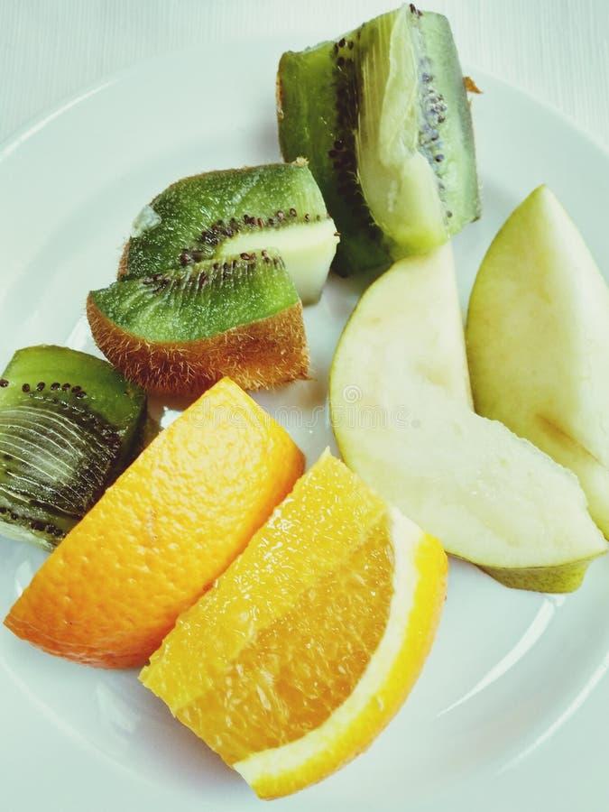 Asortowane pokrojone świeże kiwi owoc, pomarańcze, bonkrety na talerzu, odgórny widok Fotografujący na mobilnym smartphone obrazy royalty free