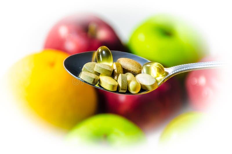 Asortowane witaminy i odżywczy nadprogramy w porci łyżce zdjęcie stock
