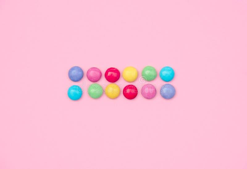Asortowani barwioni cukierki na różowym tle obraz royalty free