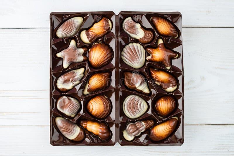 Asortowani czekoladowi cukierki skorupy kształtują w pudełku na ligh obrazy stock