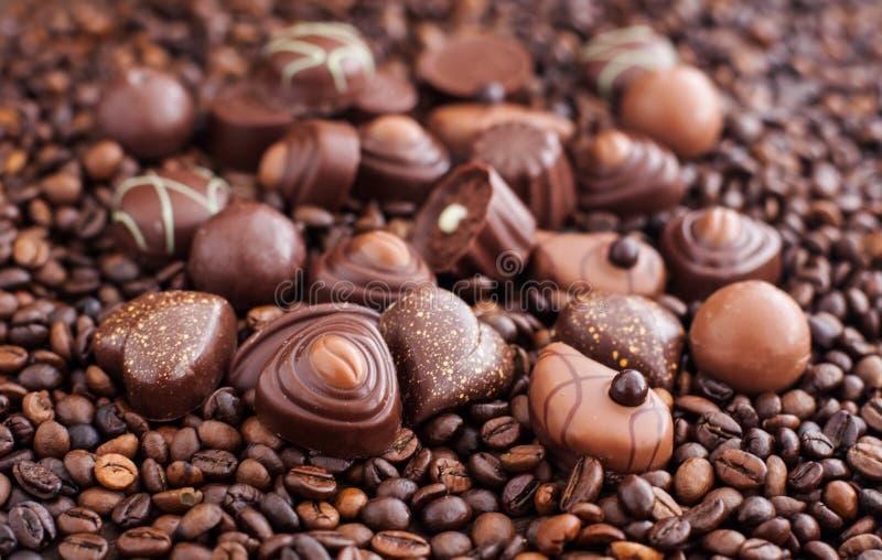 Asortowani czekoladowi pralines na kawowych fasoli tle fotografia stock