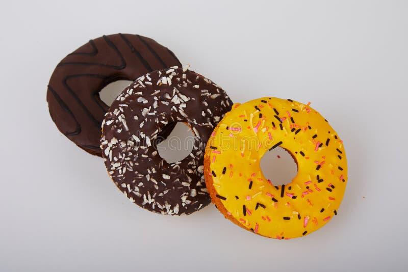 Asortowani donuts z czekoladą oszroniejącą, kolor żółty glazurowali donuts i kropią fotografia stock
